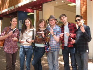 A group poses with their poem scrolls on the Charlottesville Downtown Mall.