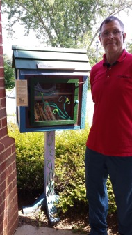 Tom Walsh, a longtime volunteer and substitute for the Greene County Library, stands beside the Little Free Library.